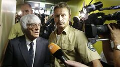 Formula One boss Bernie Ecclestone leaves the regional court in Munich, southern Germany, Tuesday, Aug.5, 2014. German prosecutors said Tuesday that they will accept dropping the bribery case against Ecclestone in exchange for a US dollar 100 million payment by the Formula One boss, and judges were considering whether to close his trial. Ecclestone went on trial at the Munich state court in late April on charges of bribery and incitement to breach of trust — which could, if he were convicted, carry a sentence of up to 10 years in prison. (AP Photo/Matthias Schrader)