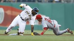 Pittsburgh Pirates' Josh Harrison, left, slides past St. Louis Cardinals second baseman Kolten Wong with a double in the first inning of the baseball game Monday, Aug. 25, 2014, in Pittsburgh. (AP Photo/Keith Srakocic)