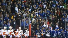 Referees get in the way of Vancouver Canucks head coach John Tortorella as he screams at the Calgary Flames bench during first period NHL hockey action at Rogers Arena in Vancouver, B.C. Saturday, January 18, 2014. THE CANADIAN PRESS/Jonathan Hayward