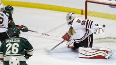 Minnesota Wild left wing Erik Haula, top left, of Finland, scores on Chicago Blackhawks goalie Corey Crawford (50) during the third period of Game 3 of an NHL hockey second-round playoff series in St. Paul, Minn., Tuesday, May 6, 2014. The Wild won 4-0. (AP Photo/Ann Heisenfelt)