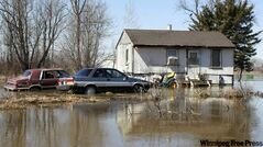 Water surrounds a home on the Peguis First Nation from the swollen Fisher River. The residents of the home have left and the pets are being cared for by volunteers.