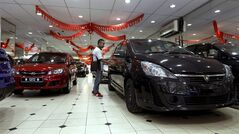 A man looks at a new car at a car showroom in Kuala Lumpur, Malaysia, Monday, Jan. 20, 2014. Malaysia's government unveiled Monday a new auto policy, offering incentives and easing curbs on the production of small, energy-efficient cars as it vies for investment with neighboring rivals Thailand and Indonesia. (AP Photo/Daniel Chan)