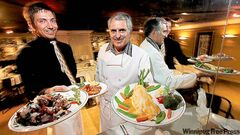 .Orlando (far left) and Arnaldo Carreira show off barbecue octopus, shrimp Orlando and orange roughy in shrimp sauce.