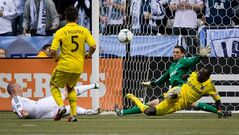 Columbus Crew's Dominic Oduro, right, of Ghana, blocks a shot by Vancouver Whitecaps' Kenny Miller, left, of Scotland, as Columbus' Danny O'Rourke, second left, watches in front of goalkeeper Andy Gruenebaum during the first half of an MLS soccer game in Vancouver, B.C., on Saturday March 9, 2013. THE CANADIAN PRESS/Darryl Dyck