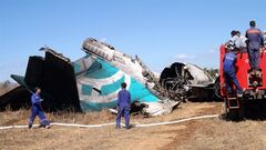 Members of Myanmar Fire Brigade team gather near a damaged Air Bagan passenger plane in Heho, Shan State, Myanmar, Tuesday. The Air Bagan flight packed with Christmas tourists crash-landed on a road in central Myanmar on Tuesday, killing two people and injuring 11, officials said. Four foreigners were among the injured, state television reported. It said the fatalities included an 11-year-old passenger believed to be a Myanmar citizen and a man riding a motorcycle on the road where the plane came down.