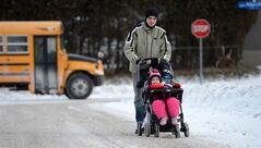 A father pushes his children in a stroller as they make their way to daycare in -20C degree weather in Ottawa on Tuesday, January 22, 2013. THE CANADIAN PRESS/Sean Kilpatrick