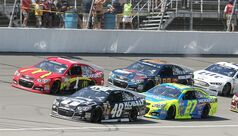 Jimmie Johnson (48) leads Jamie McMurray (1), Paul Menard (27) and Dale Earnhardt Jr. (88) during a restart of the NASCAR Quicken Loans 400 auto race at Michigan International Speedway in Brooklyn, Mich., Sunday, June 15, 2014. (AP Photo/Bob Brodbeck)