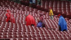 Fans in ponchos leave the stands in the rain as they wait for the start of the baseball game between the Los Angeles Dodgers and the Cincinnati Reds in Cincinnati Tuesday June 10, 2014. (AP Photo/Tom Uhlman)