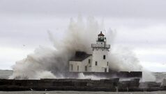 Waves pound a lighthouse on the shores of Lake Erie Tuesday as superstorm Sandy moves inland.