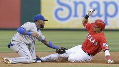 Toronto Blue Jays shortstop Jose Reyes, left, tags Texas Rangers Leonys Martin out while trying to steal second base during the third inning of a baseball game in Arlington, Texas, Friday, May 16, 2014. (AP Photo/LM Otero)