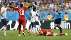 Switzerland's Johan Djourou (20) signals to referee Sander Van Roekel, of the Netherlands, as Steve von Bergen lies on the ground after getting hit by France's Olivier Giroud during the group E World Cup soccer match between Switzerland and France at the Arena Fonte Nova in Salvador, Brazil, Friday, June 20, 2014. (AP Photo/Natacha Pisarenko)