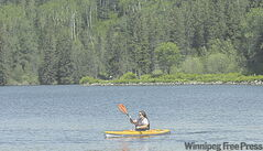 A kayaker paddles along the shore of Clear Lake near the Clear Lake Golf Course in Riding Mountain National Park.
