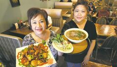 Kiet Tran ,left, owner with crispy shrimp with hot salt peppers and Melanie La with deluxe pho soup at Pho Kim Tuong restaurant at 856 Ellice ave