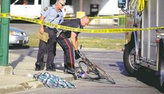 A Winnipeg police officer removes a bike from the scene of a collision between a bicycle and a semi-trailer truck on Monday afternoon.