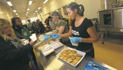 Photos by Phil Hossack / Winnipeg Free Press  Reese Precourt hands out cookies to patrons Friday at the Lighthouse Mission's soup kitchen. Precourt baked cookies to raise money for the kitchen's renovations.