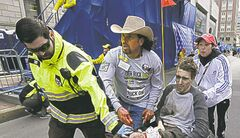 Carlos Arredondo pushes Jeff Bauman in a wheelchair after he was injured.