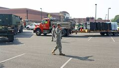 Ohio Army National Guard Spc. Luis Cardenas directs military vehicles carrying fresh drinking water, Sunday, Aug. 3, 2014, at Woodward High School in Toledo, Ohio. More tests are needed to ensure that toxins are out of Toledo's water supply, the mayor said Sunday, instructing the 400,000 people in the region to avoid drinking tap water for a second day. Toledo officials issued the warning early Saturday after tests at one treatment plant showed two sample readings for microsystin above the standard for consumption, possibly because of algae on Lake Erie. (AP Photo/Haraz N. Ghanbari)