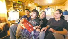 Suzanne Martin (centre), with boyfriend Nathan Sutherland, nephew Hayden Scott and sister Tiffany Martin, in one of the traditional log houses being built on the Swan Lake reserve.