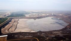 A tailings pond at the Syncrude oilsands facility is seen from a helicopter near Fort McMurray, Alta., July 10, 2012. A new report says some of the world's costliest energy projects are in Alberta's oilsands and many could be cancelled without higher oil prices. THE CANADIAN PRESS/Jeff McIntosh