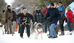Askhim pulls Kirsty Kozie away from the start line as Kirk Stubner shous encouragement at the 6th annual Snow Motion Classic, in Birds Hill Park, Sunday.