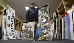 Jeffrey Bannon holds photographs of Bombers greats, including Jack Jacobs (27), among items for sale.