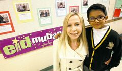 Kaleem Siddiqui, 6, his teacher, Nancy Jacobson, and the Eid mubarak ('blessed Eid')  banner he provided for his Grade 2 class at St. John's-Ravenscourt School.