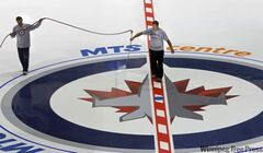 Derek King, manager of ice operations mists with water the new Winnipeg Jets fabric logo placed at center ice in the MTS Centre Friday.
