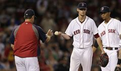 Boston Red Sox starting pitcher Clay Buchholz hands the ball to manager John Farrell as he is taken out of a game against the Toronto Blue Jays during the sixth inning of a baseball game at Fenway Park in Boston, Monday, July 28, 2014. Buchholz gave up seven runs, all earned, on seven hits in his outing. (AP Photo/Charles Krupa)