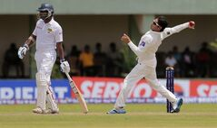 Pakistani cricketer Saeed Ajmal, right, bowls as Sri Lankan batsman Kumar Sangakkara stands beside during the fourth day of the first test cricket match between Sri Lanka and Pakistan in Galle, Sri Lanka, Saturday, Aug. 9, 2014. (AP Photo/Eranga Jayawardena)