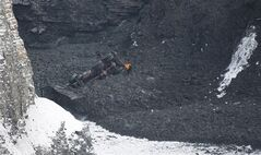 A rescue worker checks out a buried vehicle at a quarry in L'Epiphanie, Que., Tuesday, January 29, 2013. A dramatic rescue operation is underway following an apparent landslide at the quarry, with two workers missing. They are trapped under the earth at a gravel quarry just east of Montreal. THE CANADIAN PRESS/Graham Hughes.