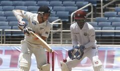 New Zealand's batsman Tom Latham, left, plays a shot as West Indies' wicket keeper and captain Denesh Ramdin looks on during the second innings on the fourth day of their first cricket Test match in Kingston, Jamaica, Wednesday, June 11, 2014. (AP Photo/Arnulfo Franco)