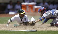 Oakland Athletics' Yoenis Cespedes, left, slides to score past the tag of Texas Rangers catcher Robinson Chirinos in the fifth inning of a baseball game Wednesday, June 18, 2014, in Oakland, Calif. Cespedes scored on a double by Brandon Moss. (AP Photo/Ben Margot)