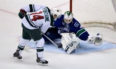 Minnesota Wild's Justin Fontaine, left, puts the puck under the leg of Vancouver Canucks' goalie Eddie Lack, of Sweden, to score the winning and only goal of the shootout during the 7th round of shooters during NHL hockey action in Vancouver, B.C., on Friday February 28, 2014. THE CANADIAN PRESS/Darryl Dyck