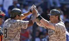 San Diego Padres' Yasmani Grandal, right, is greeted by teammate Carlos Quentin after hitting a two-run home run against the San Francisco Giants in the eighth inning of a baseball game on Sunday, July 6, 2014, in San Diego. (AP Photo/Lenny Ignelzi)