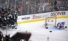 Members of the Los Angeles Kings, left, celebrate as they win in double overtime as New York Rangers goalie Henrik Lundqvist, right, of Sweden, looks on during the second overtime period in Game 5 of an NHL hockey Stanley Cup finals, Friday, June 13, 2014, in Los Angeles. (AP Photo/Mark J. Terrill)