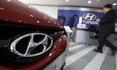 The logo of Hyundai Motor Co. is seen on a car at the automaker's showroom in Seoul, South Korea, Thursday, Jan. 23, 2014. Hyundai Motor Co. said its fourth-quarter profit increased 13 percent over a year earlier thanks to higher overseas sales. (AP Photo/Lee Jin-man)