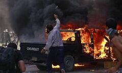 Egyptian protesters throw stones next to a burning police car during clashes  near the U.S. Embassy in Cairo on Thursday.