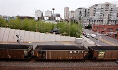 FILE - In this May, 29, 2012, file photo, a train hauling coal from an Arch Coal Inc. mine in the Powder River basin of Montana and Wyoming heads north out of downtown Seattle. A 10 percent reduction in carbon dioxide emissions will mean a decline of 180 million tons, or 18 percent, in U.S. coal production, according to Bernstein Research. That would hurt miners such as Peabody Energy, Alpha Natural Resources and Arch Coal. (AP Photo/Elaine Thompson, File)