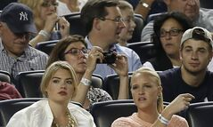 Supermodel Kate Upton, left, sits in the seats above the Detroit Tigers dugout in a baseball game between the Tigers and the New York Yankees at Yankee Stadium in New York, Monday, Aug. 4, 2014. (AP Photo/Kathy Willens)