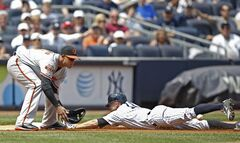 New York Yankees' Brett Gardner, right, slides into third on a first-inning triple as Baltimore Orioles third baseman Manny Machado waits for the throw during a baseball game at Yankee Stadium in New York, Sunday, June 22, 2014. Gardner was ruled safe by the third base umpire but the call was reversed after Orioles manager Buck Showalter challenged and won the call. (AP Photo/Kathy Willens)