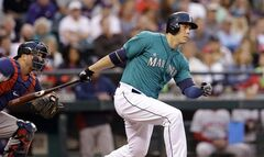 Seattle Mariners' Logan Morrison, right, singles in a run as Boston Red Sox catcher A.J. Pierzynski looks on in the fifth inning of baseball game Monday, June 23, 2014, in Seattle. (AP Photo/Elaine Thompson)