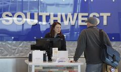 A Southwest Airlines agent helps a traveler in Dallas, Nov. 27, 2013. THE CANADIAN PRESS/AP, LM Otero