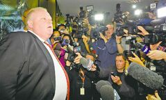 Toronto Mayor Rob Ford talks to media Thursday. He's not going anywhere despite police confirmation they have seized a video media allege shows him smoking crack cocaine.
