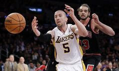 Los Angeles Lakers guard Steve Blake, left, loses control of the ball as Chicago Bulls' Joakim Noah looks on during the first half of an NBA basketball game in Los Angeles, Sunday, Feb. 9, 2014. (AP Photo/Chris Carlson)
