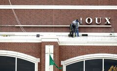 FILE - In an Oct. 22, 2012 file photo, sign company employees remove the letter S from the word Sioux as the signage proclaiming Ralph Engelstad Arena in Grand Forks, N.D.