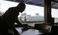 A worker busses a table at Ivar's Acres of Clams restaurant in view of a nearby docked state ferry on the Seattle waterfront Wednesday, May 14, 2014. While the Seattle mayor is proposing to raise the minimum wage to $15 in the coming years to the highest level in the nation, some activists say that's too slow and are threatening to take the issue to voters with a ballot measure that would force a raise sooner. (AP Photo/)