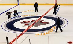 Ice technicians lay out the logos for the Jets at centre ice at the MTS Centre this morning in preparation for the start of the shortened NHL season.