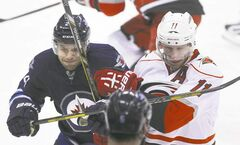 The Jets' Grant Clitsome (left) and the Canes' Jordan Staal collide in first-period action at the MTS Centre Thursday evening.