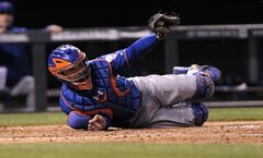 New York Mets catcher Travis d'Arnaud shows the ball in his mitt to the home plate umpire after Colorado Rockies' Charlie Culberson scored in the fourth inning of a baseball game in Denver, Thursday, May 1, 2014. (AP Photo/Joe Mahoney)