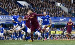 Manchester City's Carlos Tevez, centre left, is challenged by Everton's Seamus Coleman, bottom left, during their English Premier League soccer match at Goodison Park Stadium, Liverpool, England, Saturday March 16, 2013. (AP Photo/Jon Super)